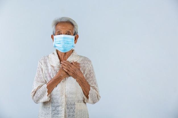 La abuela pone las manos en la cerradura y espera lo mejor.- campaña de máscara de cencept Foto gratis