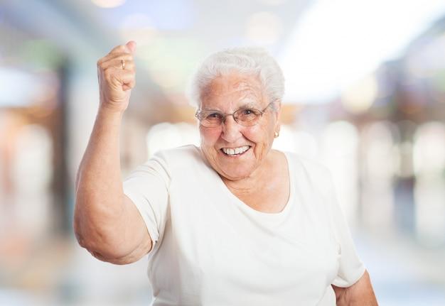 Abuela sonriendo con el puño en alto | Foto Gratis