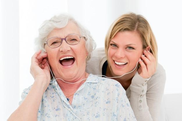 Abuela súper feliz y emocionada escuchando música con su nieta en casa Foto Premium