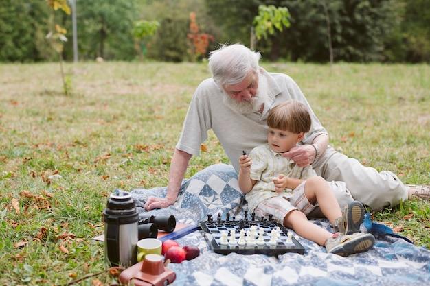 Abuelo abrazando a nieto y jugando ajedrez Foto gratis