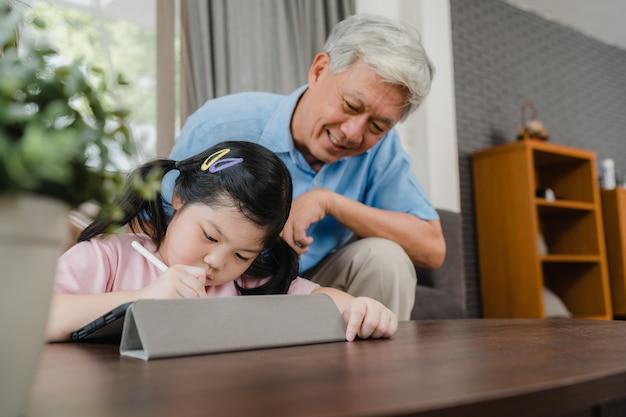 El abuelo asiático enseña a la nieta a dibujar y hacer los deberes en casa. los chinos mayores, abuelo feliz se relajan con el concepto de la chica joven que miente en el sofá en sala de estar en casa. Foto gratis