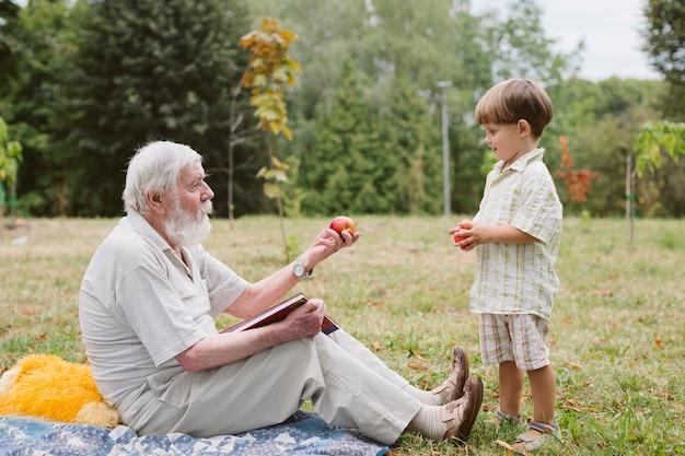 Abuelo dando manzana a nieto Foto gratis