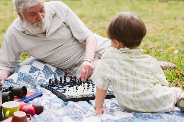Abuelo enseñando nieto ajedrez Foto gratis
