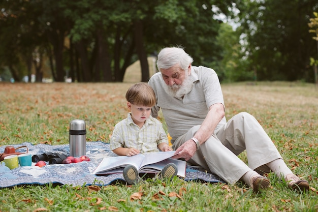 Abuelo enseñando a nieto a leer Foto gratis
