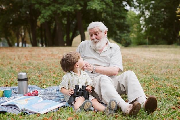 Abuelo enseñando a nieto sobre binoculares Foto gratis