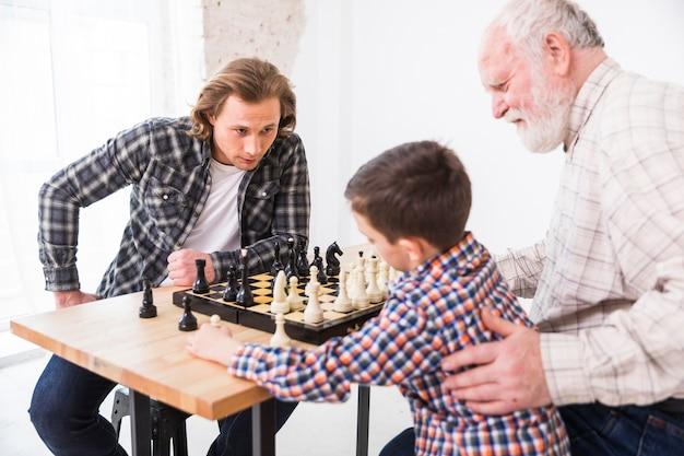 Abuelo, enseñanza, nieto, jugando al ajedrez Foto gratis