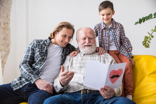Abuelo feliz mirando a través de tarjetas de felicitación hechas a mano Foto gratis