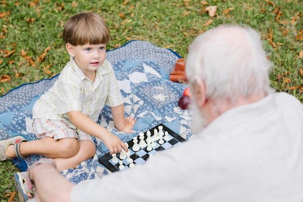Abuelo y nieto jugando ajedrez Foto gratis