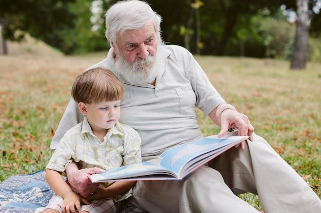 Abuelo y nieto en parque leyendo Foto gratis