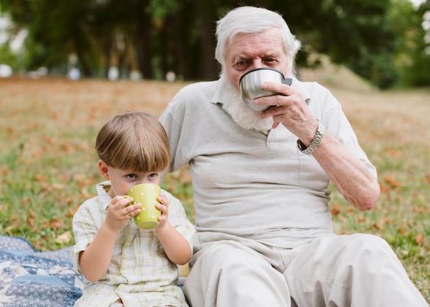 Abuelo y nieto en picnic tomando té Foto gratis