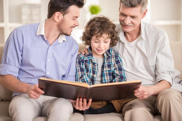 Abuelo, padre e hijo sentado y leyendo libro en sofá Foto Premium
