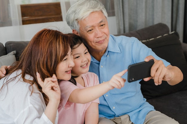 Abuelos asiáticos selfie con nieta en casa. los chinos mayores, el abuelo y la abuela felices pasan el tiempo en familia relajándose usando el teléfono móvil con el niño de la niña acostado en el sofá en concepto de sala de estar. Foto gratis