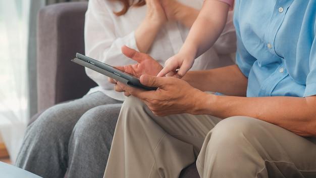 Abuelos y nieta asiáticos que usan la tableta en casa. senior chino, abuelo y abuela feliz pasar tiempo familiar relajarse con una niña revisando las redes sociales, acostado en el sofá en concepto de sala de estar Foto gratis