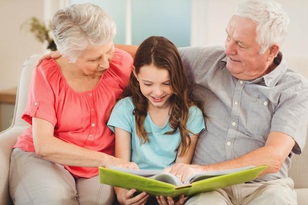 Abuelos y nieta sentados en el sofá y leyendo un libro con nieta Foto Premium