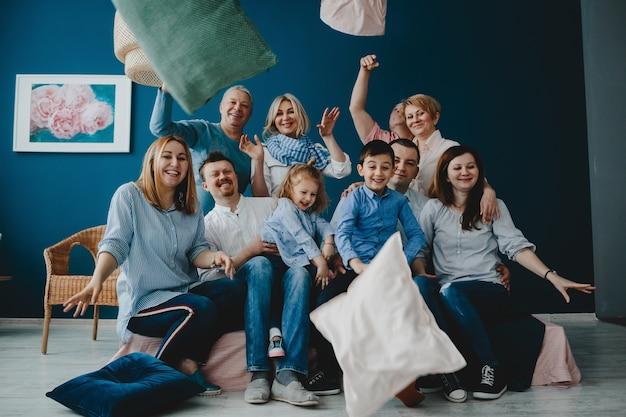 Abuelos, padres y sus pequeños hijos se sientan juntos en la cama en una habitación azul Foto gratis