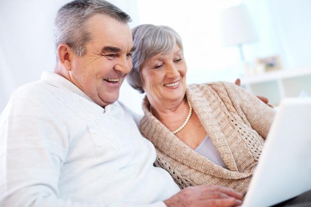 Abuelos usando el ordenador portátil Foto gratis