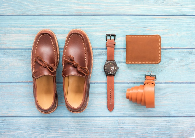 Accesorio para hombre con zapato holgazán, billetera de cuero, reloj marrón y cinturón aislado en un fondo de madera azul. vista superior. Foto Premium