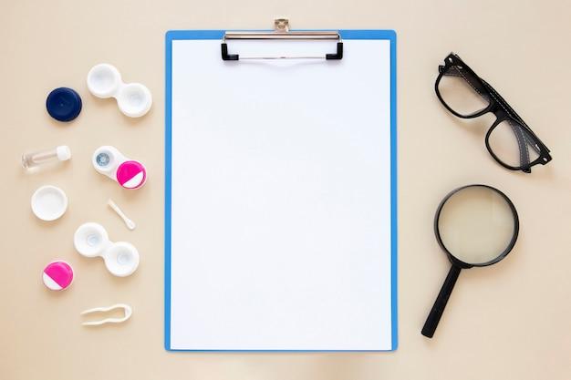 Accesorios para el cuidado de los ojos sobre fondo beige con maqueta del portapapeles Foto gratis