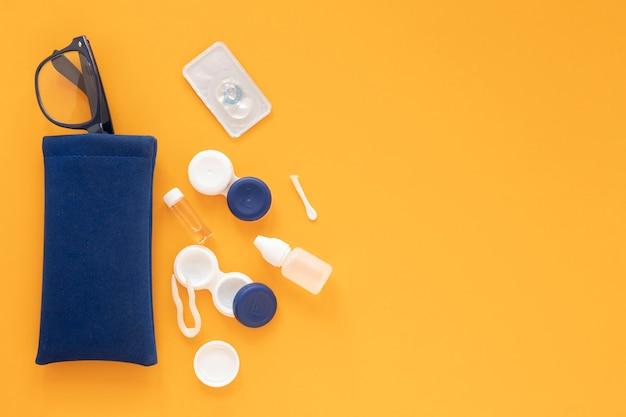 Accesorios para el cuidado de los ojos sobre fondo naranja Foto gratis