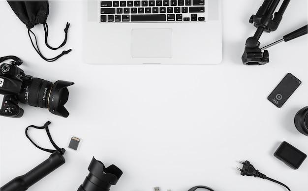 Accesorios para laptop y cámara sobre fondo blanco con espacio de copia Foto gratis