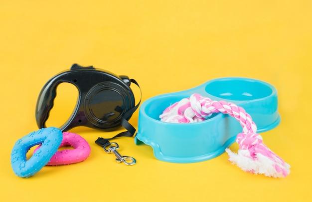 Accesorios para mascotas sobre fondo amarillo. Foto Premium