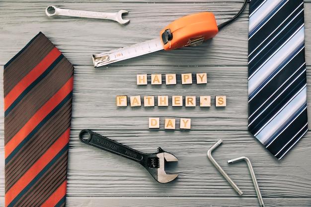 Accesorios masculinos cerca de instrumentos y felices palabras del día del padre con corbatas. Foto gratis