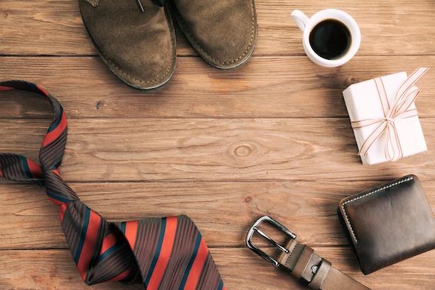 Accesorios masculinos cerca de presente y copa. Foto gratis