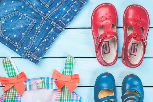 Accesorios de niña pequeña. colorido vestido, zapatos y jeans en superficie de madera azul pastel. Foto Premium