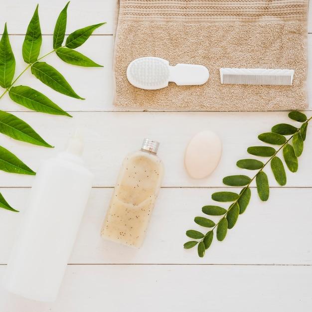 Accesorios para la salud de la piel en la mesa con hojas verdes Foto gratis