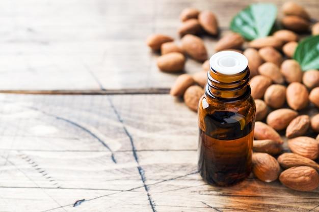 Aceite de almendras en botella en la mesa de madera. concepto spa, aromaterapia y medicina. Foto Premium