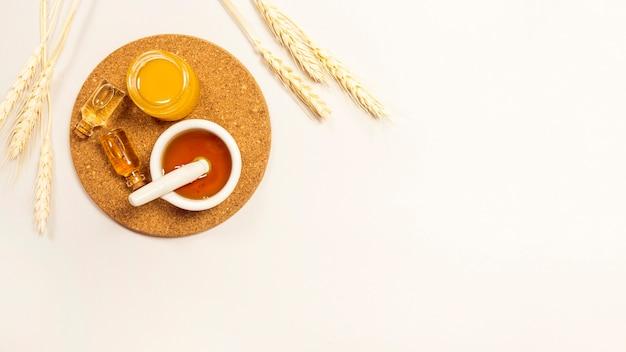 Aceite esencial y miel sobre corcho marrón con espigas contra un fondo blanco Foto gratis