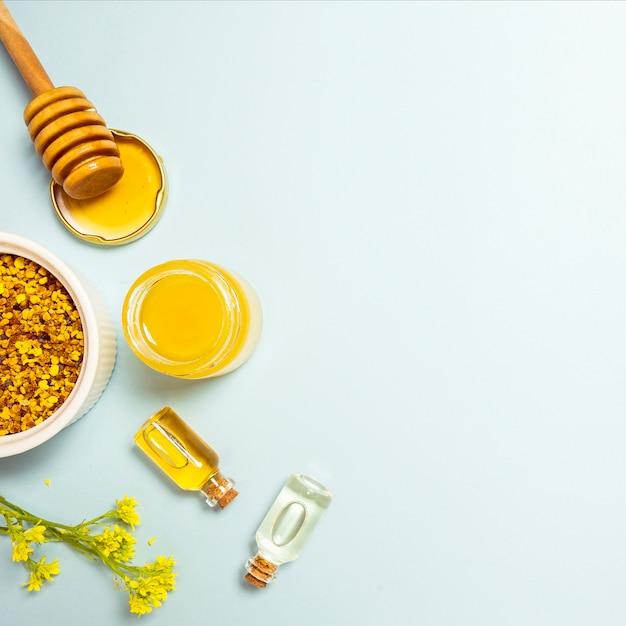 Aceite esencial; polen de abeja y miel con flor fresca amarilla sobre fondo azul Foto gratis