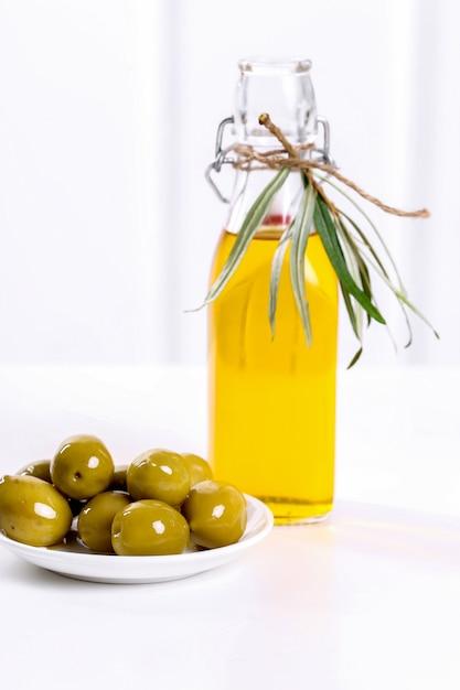 Aceite de oliva en una botella con aceitunas Foto gratis