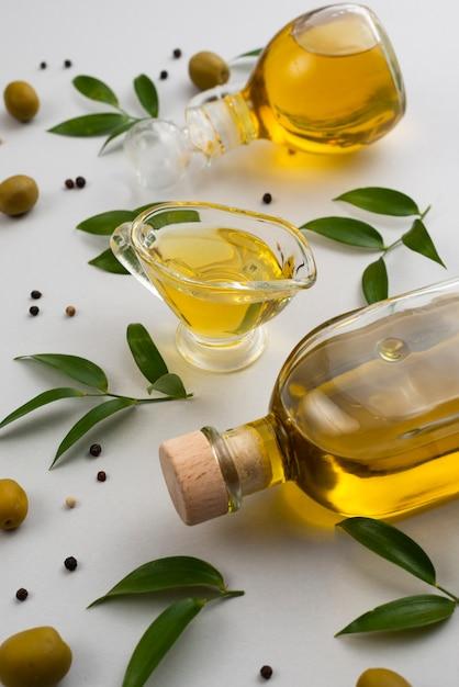 Aceite de oliva natural en botella y copa en mesa Foto gratis
