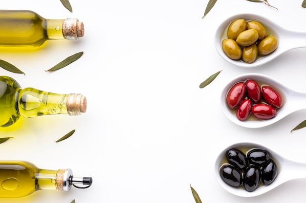 Aceitunas negras rojas amarillas en cucharas con hojas y botellas de aceite Foto gratis