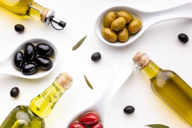 Aceitunas negras rojas amarillas planas en cucharas con botellas de aceite Foto gratis