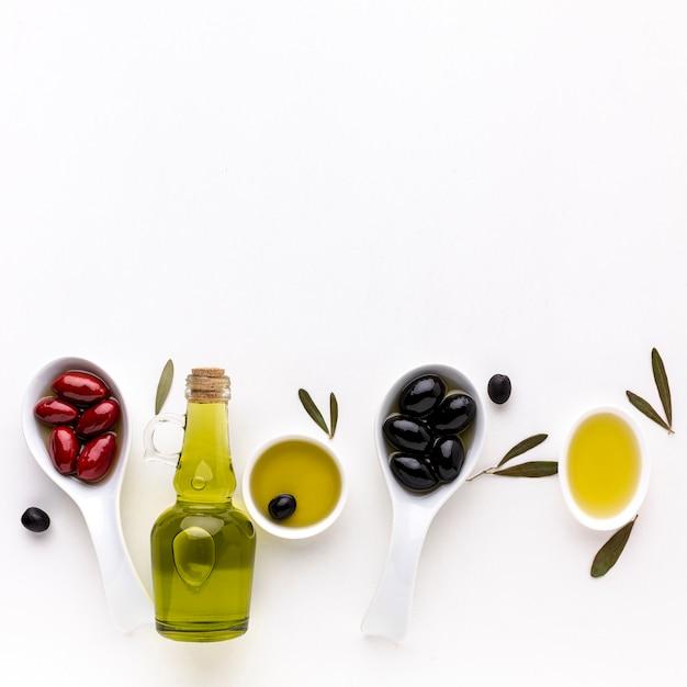 Aceitunas negras rojas en cucharas con botella de aceite Foto gratis