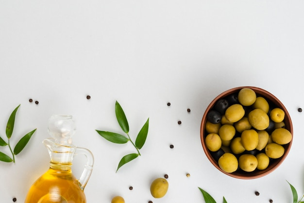 Aceitunas planas en un tazón y botella de aceite Foto gratis