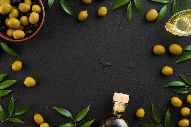 Aceitunas verdes sobre fondo negro con espacio de copia Foto gratis