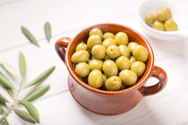 Aceitunas verdes en tazón rústico Foto Premium