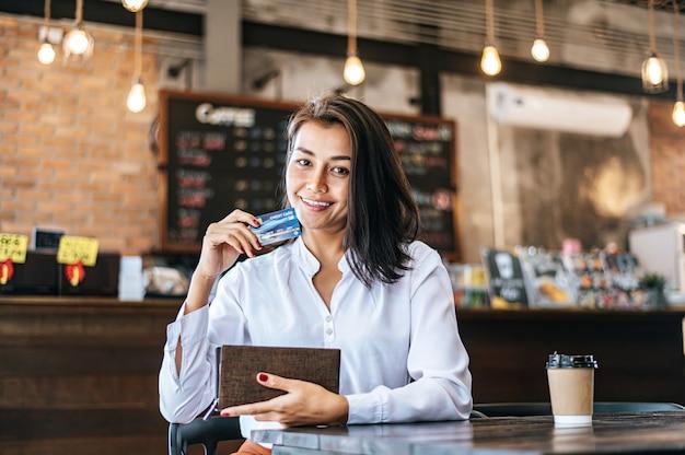 Se aceptan tarjetas de crédito de una cartera marrón para pagar los productos en pedidos de café. Foto gratis