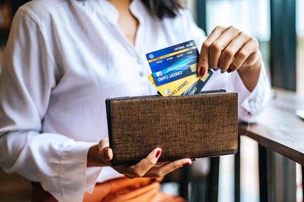 Aceptar tarjetas de crédito de una cartera marrón para pagar los bienes Foto gratis