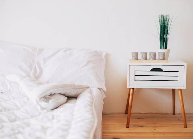 Acogedor dormitorio en color blanco con mesita de noche. Foto gratis
