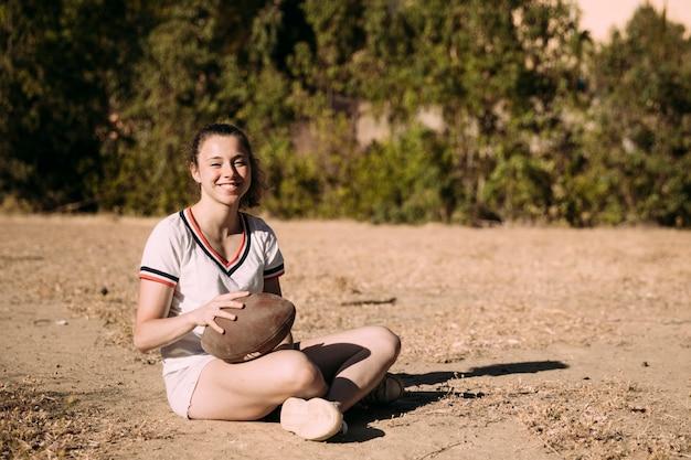 Adolescente alegre sentado con pelota de rugby Foto gratis