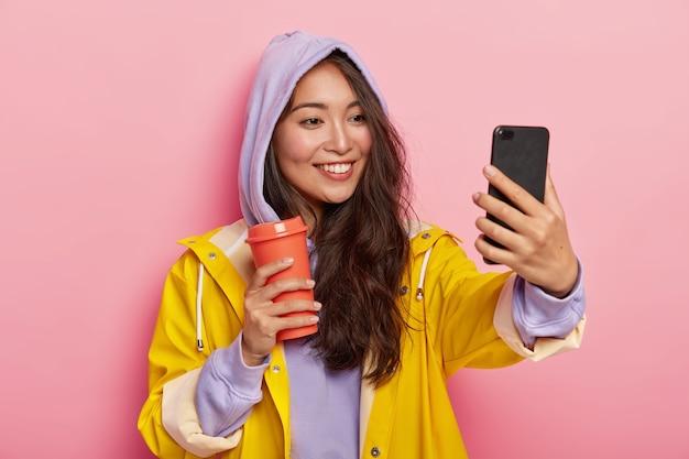 Adolescente con apariencia específica toma un retrato selfie, camina al aire libre durante el día de otoño, usa impermeable protector, bebe café del matraz Foto gratis