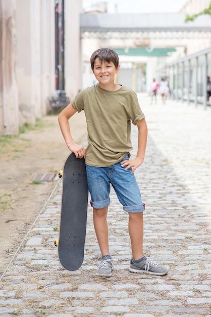 Un adolescente cargando patineta y sonriendo Foto Premium