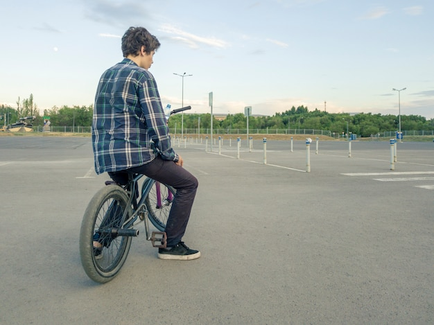Adolescente casual sentado escalofriante en bicicleta en el gran campo de deportes de asfalto Foto Premium