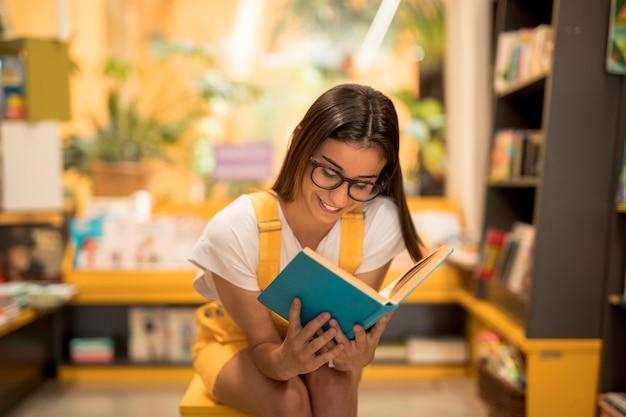 Adolescente colegiala leyendo libro cautivado Foto gratis