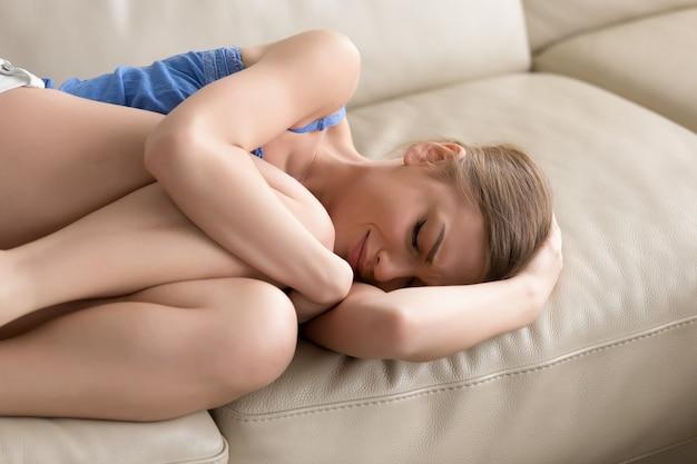 Adolescente deprimida molesta acostada en el sofá, llorando abrazando sus rodillas Foto gratis