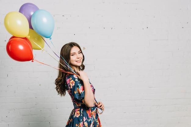 Adolescente feliz de pie contra la pared de ladrillo blanco con globos Foto gratis